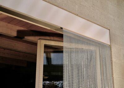 Il profilo di questa tenda è fissato alla copertura in lamiera pre-esistente di un cassonetto senza fori supplementari. La tenda chiude l'apertura della porta in modo che nessuna mosca possa entrare all'interno.