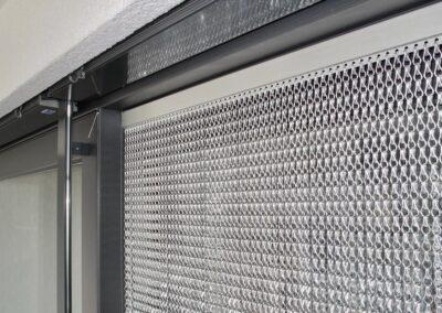 Primo piano della tenda antimosche krismar montata davanti a una porta scorrevole. Le catene di alluminio riflettono la luce del sole, impedendo alle mosche di entrare all'interno.