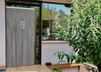 La tenda antimosche krismar è montata proprio davanti a una porta di vetro con telaio metallico, che conduce nel giardino. La vista in questa foto è diretta dal giardino verso il soggiorno, dove la tenda offre protezione visiva dall'interno.
