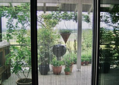 La tenda antimosche krismar è montata davanti a una terrazza coperta con un'ampia finestra frontale. In questa foto la vista è diretta dall'interno verso la terrazza piantumata. Per una piacevole ventilazione, la porta della terrazza può essere lasciata aperta in estate senza che le mosche entrino all'interno.