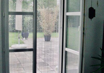 La tenda antimosche krismar è montata davanti a una porta a doppia ala che conduce al giardino. In questa foto la vista dal soggiorno è diretta verso il sedile del giardino. A causa delle delicate catene, la luce del giorno splende all'interno e la vista sul giardino è quasi non è limitata.