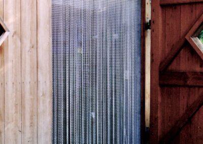 La tenda antimosche krismar montata su un recinto per animali con porte ad ala. Gli animali domestici possono facilmente passare la tenda antimosche krismar dopo un breve periodo di adattamento.