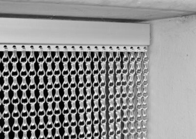 Vista dettagliata del lato anteriore del profilo, inserito con precisione in un telaio di cemento della porta. Il lato inferiore del profilo è dotato di perforazioni regolari alle quali sono fissate le catene a maglie in alluminio.