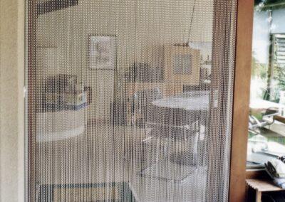 La tenda antimosche krismar montata davanti alla porta di un giardino con telaio in legno. In questa immagine, la vista del giardino è rivolta verso l'interno, mostrando la trasparenza delle catene di alluminio finemente strutturate della tenda e la facilità con cui può essere attraversata.