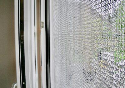 Primo piano della tenda antimosche krismar, con catene in alluminio argentato, montata davanti a una porta d'ingresso. Questa immagine mostra come la luce del giorno brilli attraverso le catene finemente strutturate all'interno e come la trasparenza delle catene non limiti la vista sul giardino.