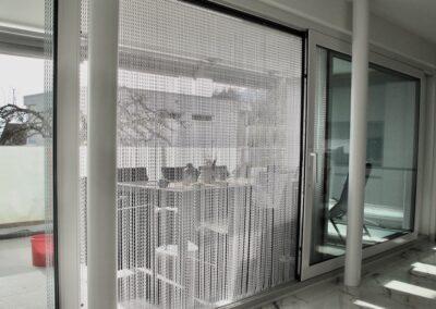 Il profilo di questa tenda è fissato alla copertura in lamiera pre-esistente di un cassonetto di una porta scorrevole per balconi con un'ampia finestra frontale. In questa foto, la vista è diretta dall'interno verso la terrazza. È ovvio che le catene di alluminio finemente strutturate non trattengono la luce del giorno e non compromettono la luminosità dell'interno e la vista verso l'esterno.